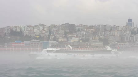enevoado : Ferry sailing past Istanbul Harbor in mist and fog above the water
