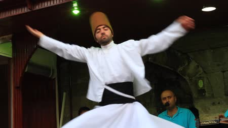 orta : ISTANBUL - JUL 25, 2012: Sufi whirling dervish (Semazen) dances at Sultanahmet during holy month of Ramadan. Semazen conveys Gods spiritual gift to those are witnessing the ritual. Whirling dervish spins with the music.