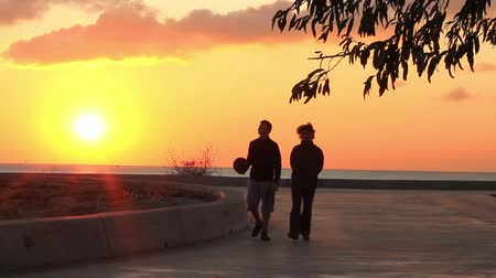 két : Sportsmen stroll on the beach at beautiful sunset