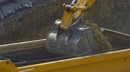 equipamento : Dump truck being loaded with soil by shovel slow motion. Close up original HD video. Construction machinery working at the construction site