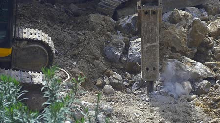 молоток : Big hydraulic rock hammer breaker. Dust in Slow Motion. Stone crusher on excavator destroying rocks in the construction site Стоковые видеозаписи
