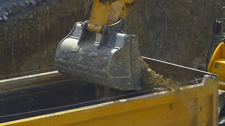 şantiye : Excavator loading soil on a dump truck. Slow motion close up video. Crawler dozer and tipper working at the construction site Stok Video