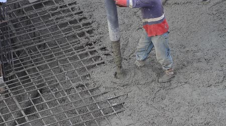 cement floor : Concreting and smoothing slab on the construction site. Construction man pouring cement on concrete footings for a house. Footings are the concrete and steel support that hold the home and keep it from sinking or shifting on the earth