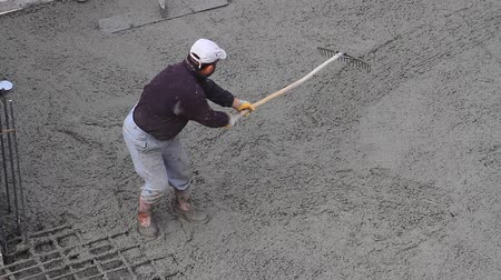 chunky : Concrete rake does a better job smoothing out chunky concrete mix. It is also a very versatile product as you can use the toothed side for raking while employing the smooth side to float and screed the materials surface. Laborer from construction industry Stock Footage