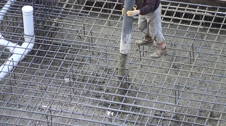 cement floor : Worker pulling a large hose for concreting of steel reinforced concrete. Construction worker during concrete pouring work at the construction site.