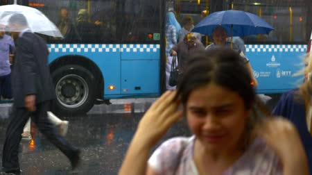 rainy : People with umbrellas in the rain at Eminonu Bus Stop running. Once its starts raining Istanbul city turns into a whole different place you never see in bright daylight. People run from rain Stock Footage