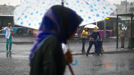 rainy : People run through an afternoon downpour. Once its starts raining Istanbul city turns into a whole different place you never see in bright daylight Stock Footage