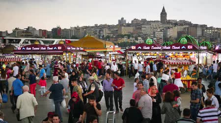 koşuşturma : Crowd of people arrive and depart from Eminonu Pier looking to Goldenhorn and Galata Tower. Hustle and bustle of people just before the rain started The in Istanbul. Timelapse view