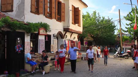 macadam : IZMIR, TURKEY - Jun 14, 2014: Sirince, lovely cluster of shops, traditional Greek houses, and restaurants is set on a lush hill; the rows of houses have decorative eaves Motifs with nature. Main street of Sirince with a wine tasting house
