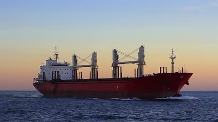 навигацион судно : Cargo ship sailing from open sea. A bulk carrier ship with deck cranes on the sunset time.