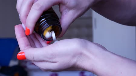 manikür : Young woman with bright manicure overdosing pills to commit suicide in the bedroom. Depressed woman committing suicide by taking a lethal dose of pills. Medication in hand. Stok Video