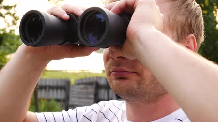 looking distance : Handsome man looks through binoculars then puts them down and looks thoughtfully into the distance. Closeup Stock Footage