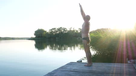 Handsome 64 years old man practicing yoga near lake at the rays of sunset. Yoga excercises. Yoga concept.