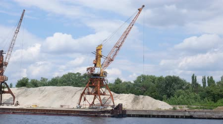 Two port cranes on the river bank produce sand of the river, sunset, barge. Port cranes with a bucket on the river bank, extraction of river sand. Port cargo cranes extracts river sand, production.