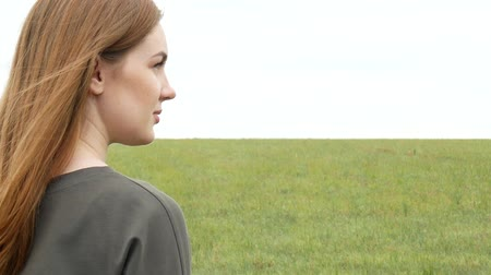 Portrait of a beautiful girl with red straight hair in khaki sweatshirt on a meadow background. Side view of young woman face Dostupné videozáznamy