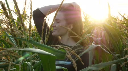 Portrait of a beautiful smiling girl with blue eyes in a corn field.