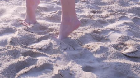 Rear view of female feet close up. Girl walking barefoot on tiptoes and turning around on sand at sunset in slow motion