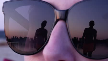 Reflection of an approaching man in female sunglasses in slow motion. Sunset summer beach Dostupné videozáznamy