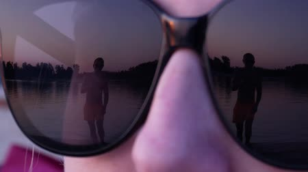 Reflection of an approaching and dancing man in female sunglasses in slow motion. Sunset summer beach