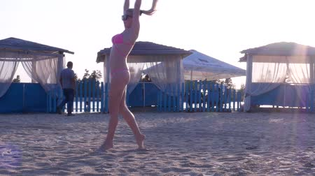 Sexy blonde girl in a pink bikini and sunglasses performing a front flip and then sits on a twine at sunset. Active life style. Slow motion