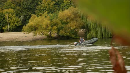 Young man rides an inflatable rubber motor boat then stops along the river near the riverbank with colorful autumn trees.