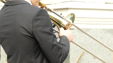 trąbka : Daytime, male trombone player during an outdoor concert of a brass band. Young man in black suit playing his trombone, side view. The trumpet in the hands of the musician closeup Wideo