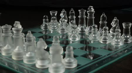 Close-up of male and female hands playing clear and frosted glass chess pieces on a glass chess board. A clear glass queen checkmates the king in 2 moves. Victory leader and success concept. Game over