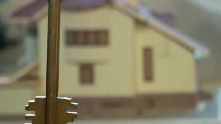 Close-up of a key held on the background of rotating private house model. Home loans, mortgage or real estate concepts