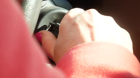 Close-up of female hand inserting a car key into egnition lock near steering wheel and starting an engine