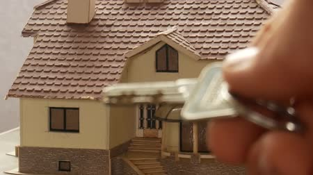Close-up of real estate agent hand giving house key to his customer on the cottage model background. Buying a new house and receiving house keys. Home loans, mortgage or real estate concepts