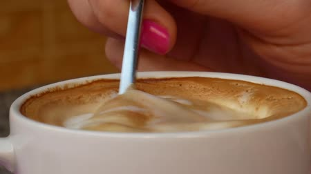Close-up of female hand stirring creamy cappuccino or coffee latte in a white cup with teaspoon before drinking