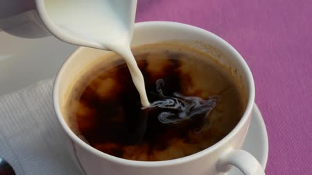 A closeup view of milk or cream being poured into a white cup of black coffee on the lilac tablecloth. Concept of coffee break. Milk poured into coffee.