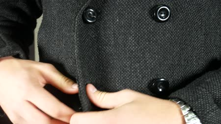 Close-up of young stylish man fastening buttons of his textile winter coat. Elegant man with wristwatch dressing up. Close up of man`s hands doing up winter jacket. Men`s beauty, seasonal fashion
