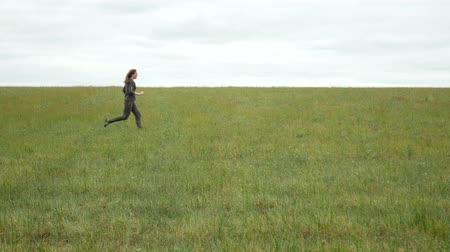 Girl with long red hair runs fast along a meadow. Beautiful young woman in khaki sport suit runs in the field. Agricultural footage.