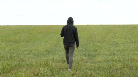 hippie : One girl in khaki sport suit and hood walks across a meadow. Sad young woman goes slowly in the field. Agricultural footage. Stock Footage