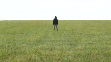 One girl in khaki sport suit and hood on her head stands in a meadow on the horizon. Sad young woman in the field. Agricultural footage. Dostupné videozáznamy