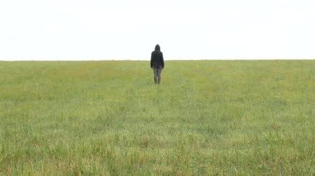 One girl in khaki sport suit and hood on her head stands straight in a meadow on the horizon. Sad young woman in the field. Agricultural footage.
