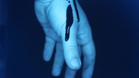 frightful : Blood on a male hand. Close-up video of a thick blood flowing down a male hand in blue lights. Stock Footage