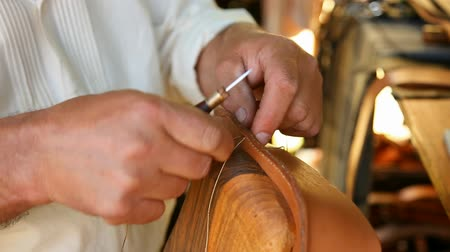 couro : Furrier sewing a piece of leather in the workshop