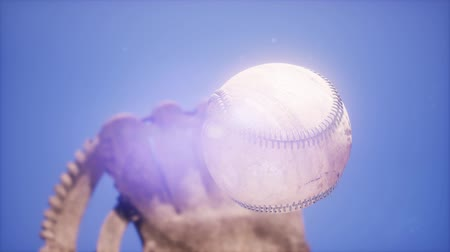yakalamak : 4K Super slow motion Baseball and mitt at blue sky background Stok Video