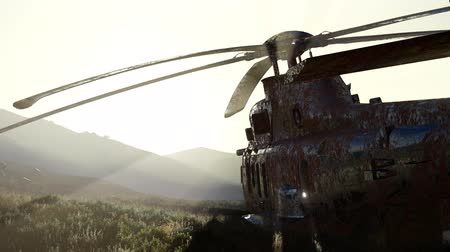 войска : old rusted military helicopter in the desert at sunset