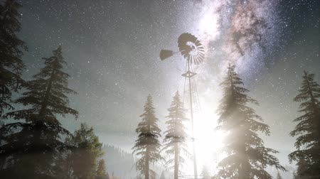 mléčný : retro windmill in mountain forest with stars. hyperlapse
