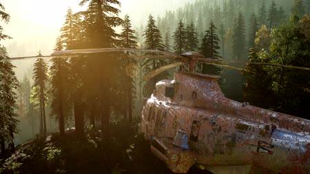 aerodrome : old rusted military helicopter in the mountain forest at sunrise Stock Footage