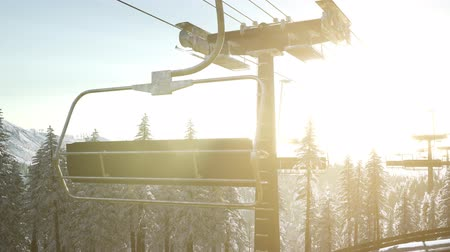 esqui : empty ski lift. chairlift silhouette on high mountain over the forest at sunset