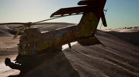 terrorizmus : old rusted military helicopter in the desert at sunset