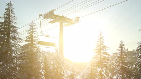 winda : empty ski lift. chairlift silhouette on high mountain over the forest at sunset