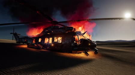 commando : burned military helicopter in the desert at sunset