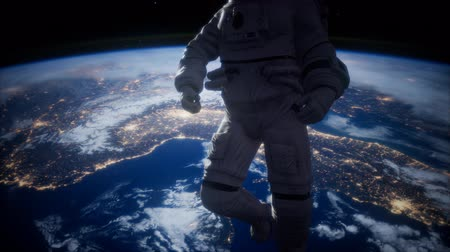 távcső : Astronaut in outer space against the backdrop of the planet earth Stock mozgókép