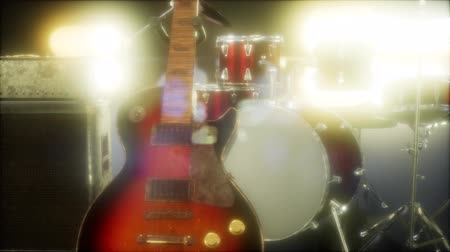 fame : Drum kit and guitar in subdued stage lighting.