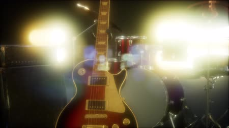 amplificador : Drum kit and guitar in subdued stage lighting.